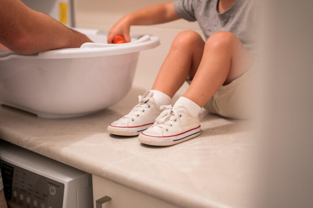 child sitting beside baby bathtub