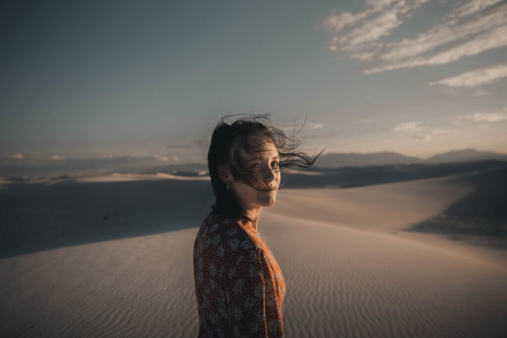 woman in white and black floral shirt standing on brown sand during daytime